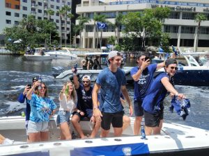 Rookies Forward Ross Colton to the right and Defenseman Callan Foote behind him with friends and family celebrating at the boat parade